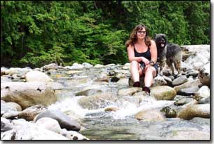Briard-Artemis and Barbara sitting by a stream in BC